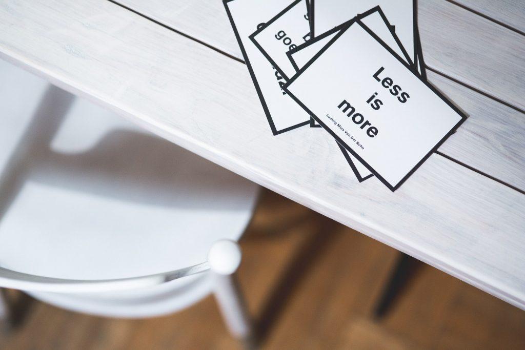 Image qui contient une table et une chaise avec des affiches Less is More représentant le minimalisme